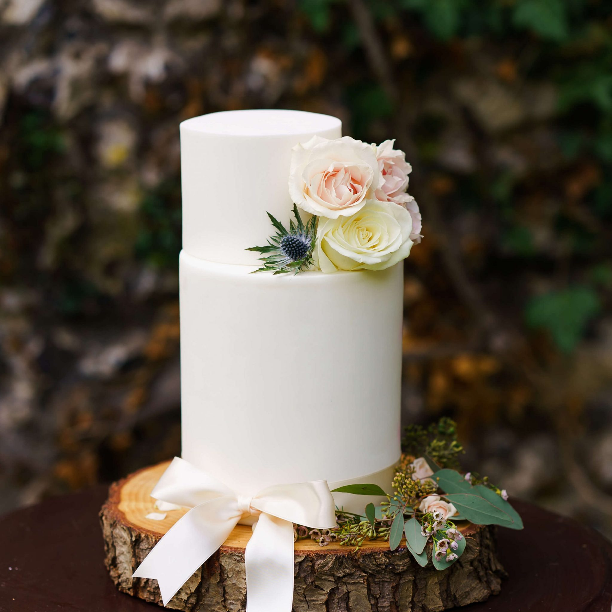 2 Tier White Wedding Cake with Fresh Flowers in Front of Garden Wall