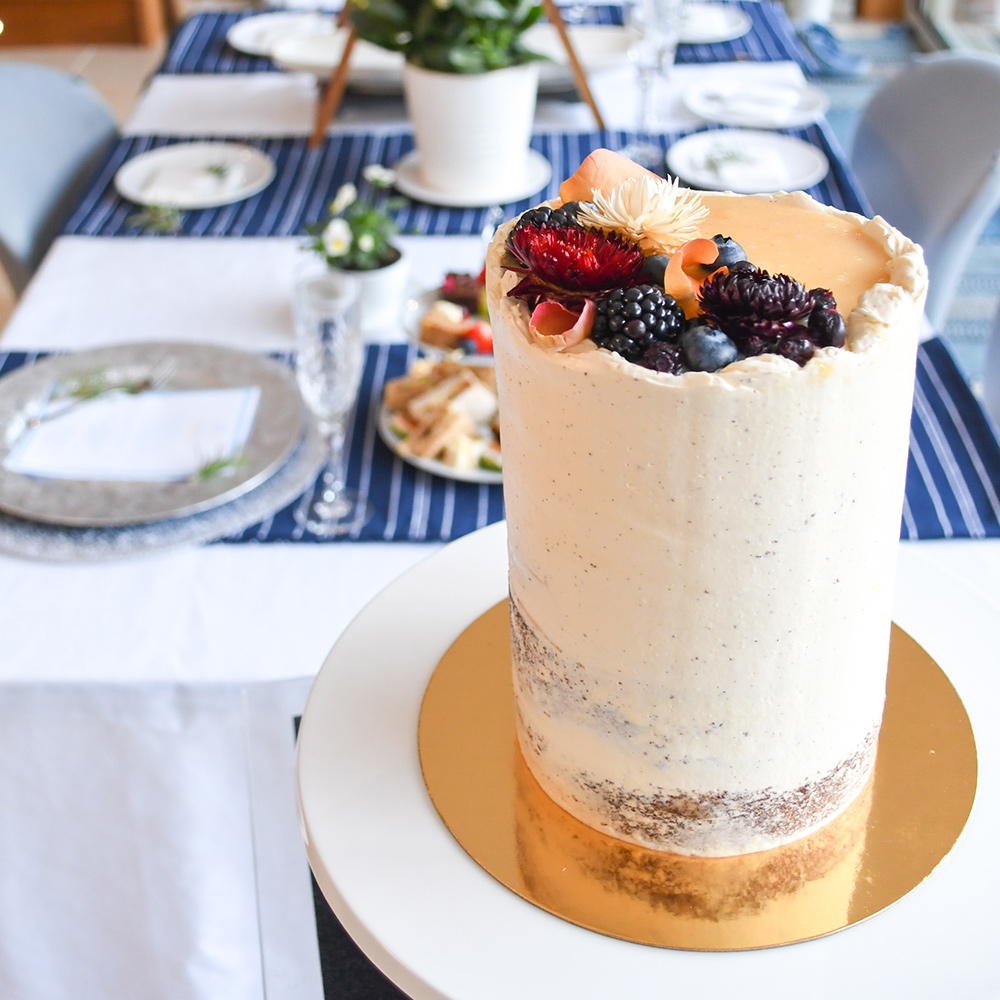 Tall Semi-Naked Wedding Cake with Black Fruits and Caramel in Front of White and Blue Table Setting