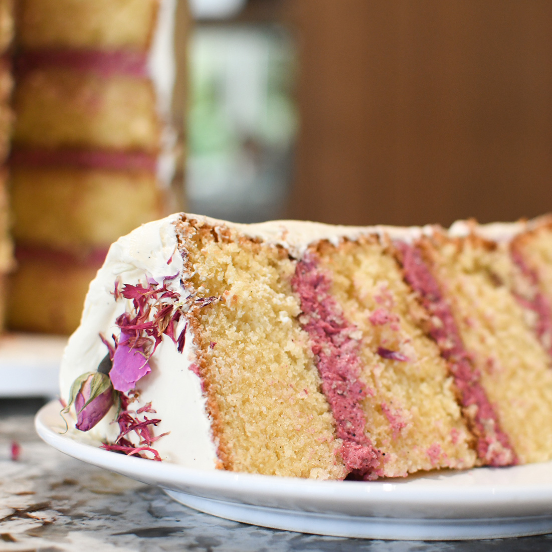 Slice of Wedding Cake with Dried Flower Petals and Pink Icing