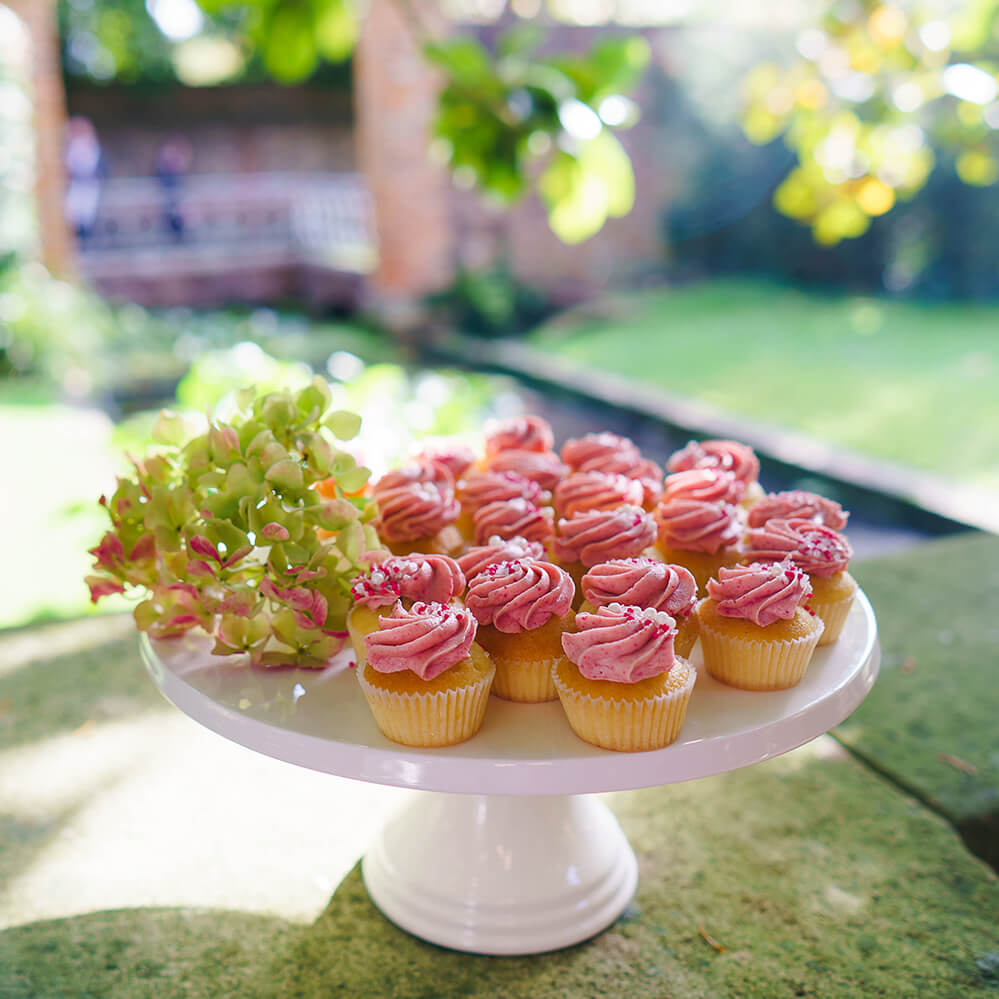 Mini Cupcakes with Pink Icing Swirl on White Cake Stand in Garden