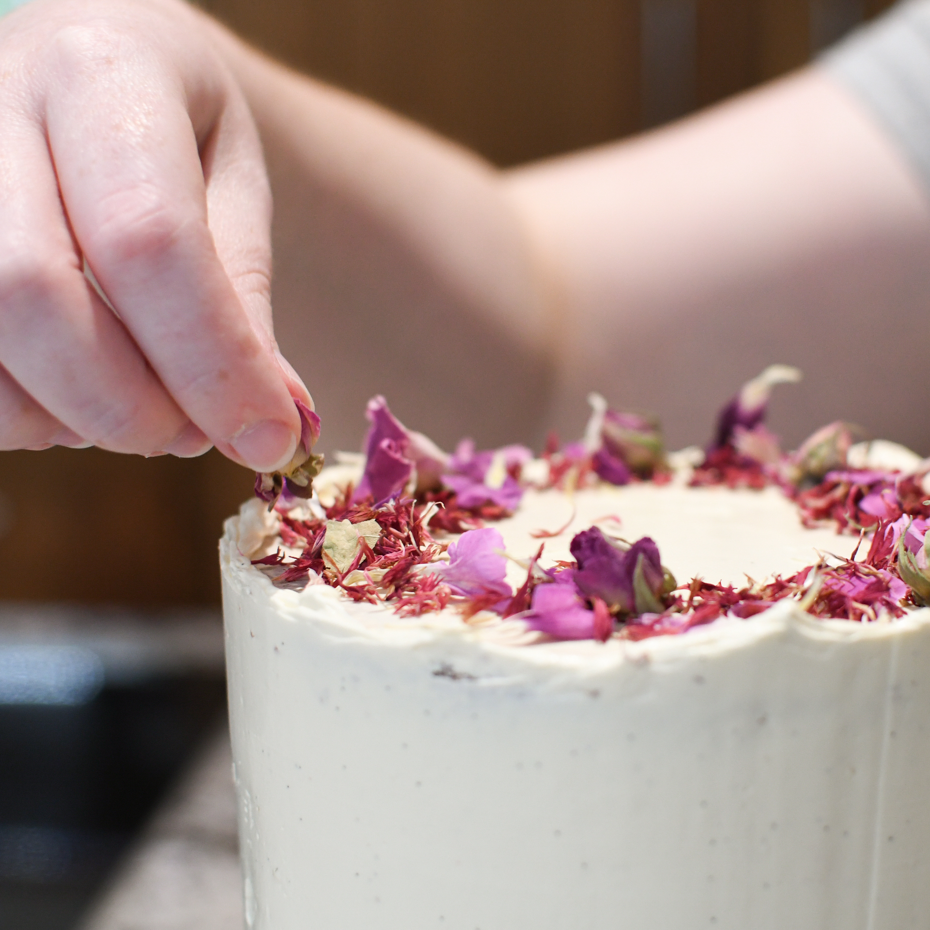 Small Wedding Cake Being Decorated with Dried Rose Petals