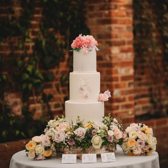 3 Tier Fondant Wedding Cake with Flowers around Bottom in Front of Brick Wall