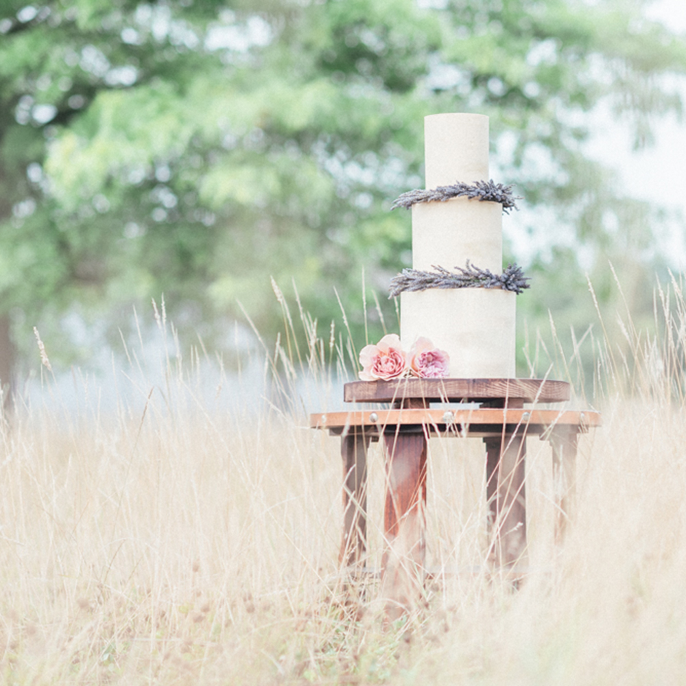 3 Tier Wedding Cake with Lavender Wreaths on a Table in a Field