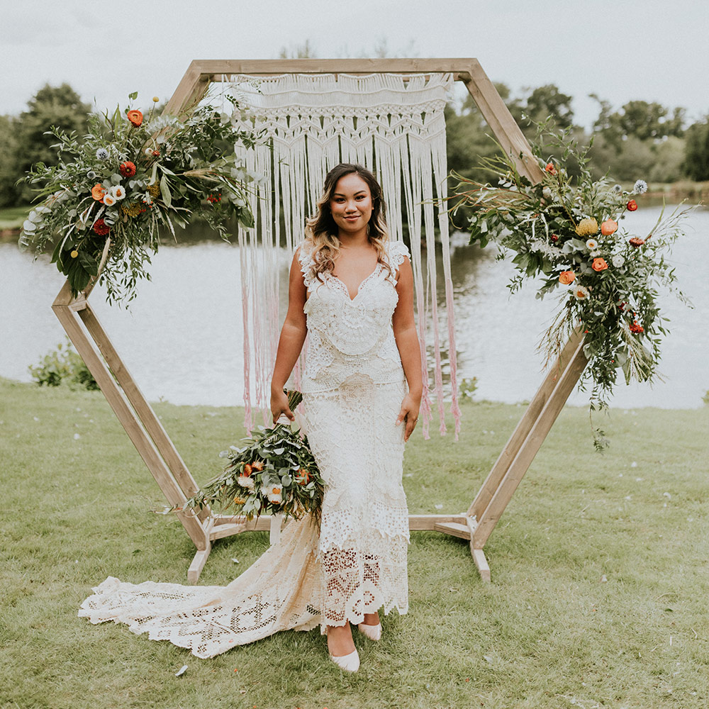 Bride Standing in Front of Wooden Hexagon Decorated with Flowers