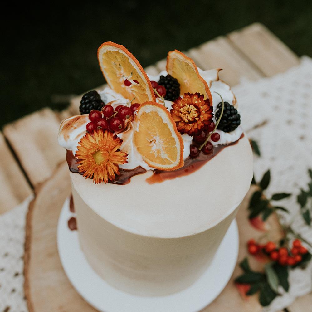 Buttercream Cake with Orange Slices, Orange Flowers, Caramel Drip, Torched Meringue and Fruit in Garden Scene